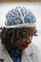 Зимняя шапка спицами с косами в виде заснеженных деревьев