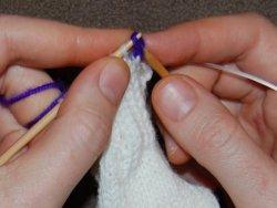 Протянуть накид над лицевой петлей, обработав ее для эластичного закрытия петли